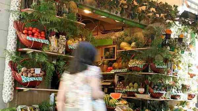 Una mujer pasa por delante de un frutería.