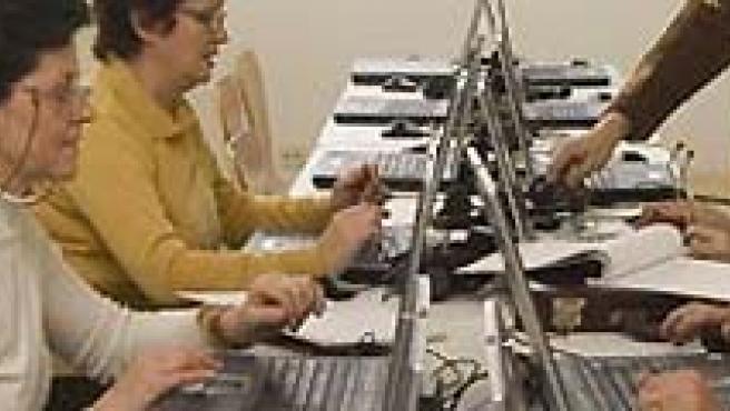 Varios jubilados, en una clase de informática.