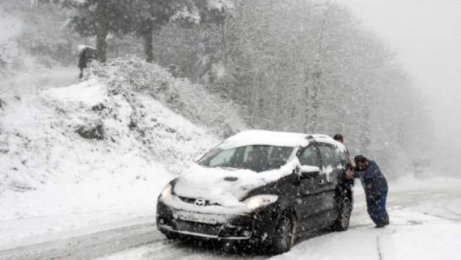 Dos personas empujan un coche en Girona durante el último temporal .