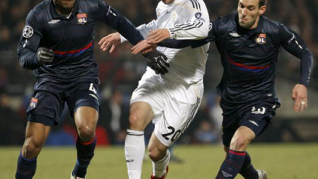 El delantero argentino del Real Madrid Gonzalo Higuaín (c) intenta escapar con el balón de Jean-Alain Boumsong (i) y Anthony Reveillere (d) del Olympique de Lyon.