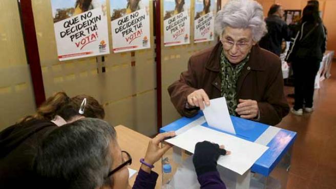Una anciana deposita su voto en el colegio electoral Centre Civic L'Estacio de El Vendrell (Tarragona).