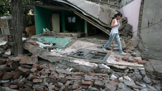 Una joven camina cerca de una vivienda destruida en Santiago (Chile), tras el terremoto que sacudió el país este sábado.