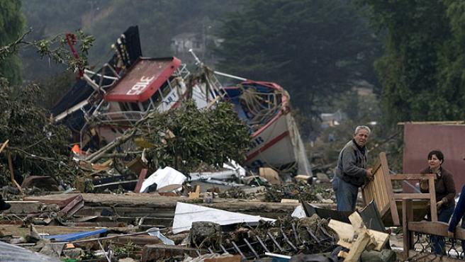 Dos personas rescatan algunas pertenencias de su hogar destruido tras el terremoto en la localidad de Dichato, Chile.
