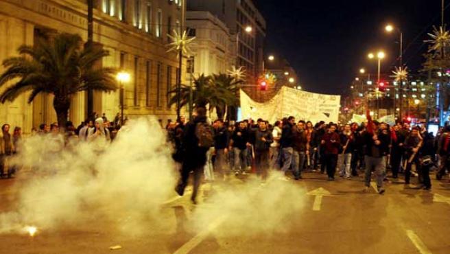 Un grupo de manifestantes intenta evadir el gas lacrimógeno lanzado por la Policía durante las protestas en Grecia.