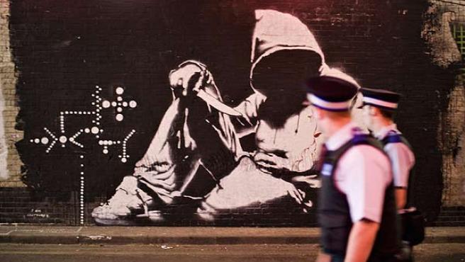 Dos policías pasan ante una obra de Bansky en Londres.