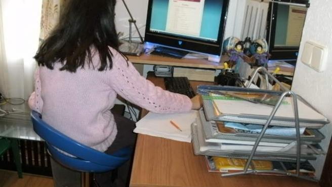 Silvia, de espaldas, hace sus deberes. Lleva 17 meses sin ir a clase por miedo a sus compañeros.
