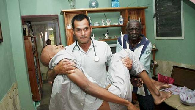 El disidente Fariñas es trasladado por un médico para llevarlo al hospital, este jueves.
