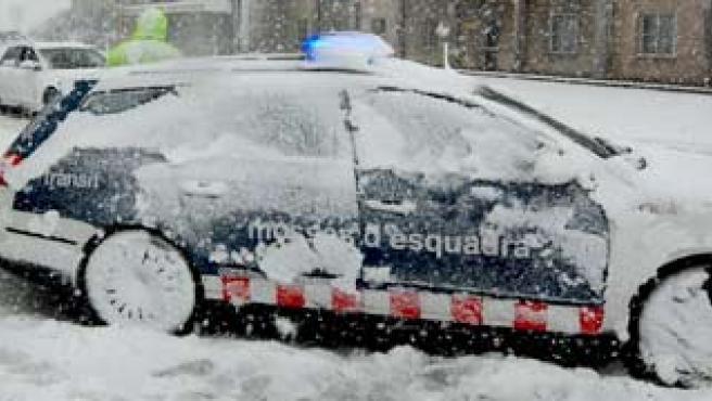 Un coche patrulla de los Mossos d'Esquadra, cubierto por la nieve.
