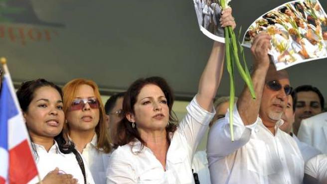 Gloria Estefan y su esposo Emilio sostienen fotografías de las Damas de Blanco de Cuba durantela marcha en favor de ese grupo en Miami.