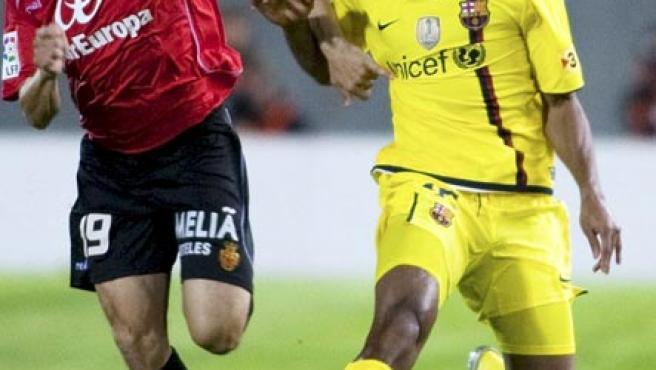 El mediocentro malí del FC Barcelona Seydou Keita (d) conduce el balón ante el centrocampista del RCD Mallorca José Luis Martí.