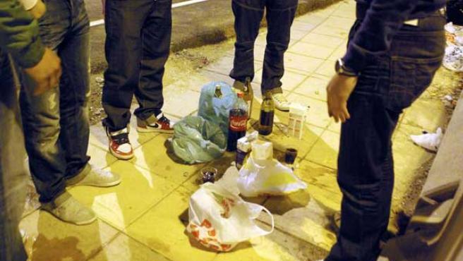 Varios jóvenes hacen botellón en la calle.