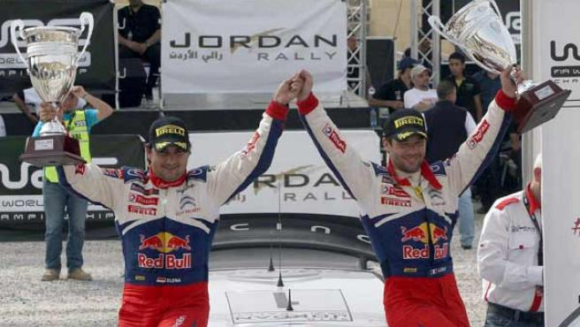 El piloto francés de Citroen Sebastien Loeb y su copiloto Daniel Elena celebran su victoria en el rally de Jordania.