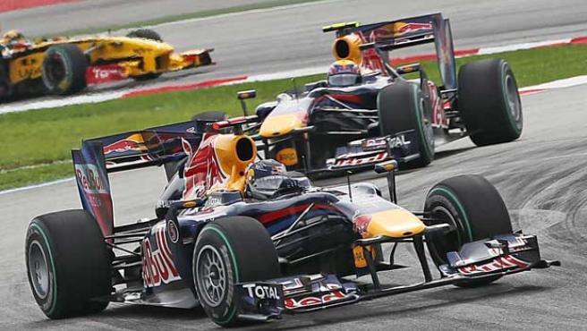 El piloto alemán Sebastian Vettel (i), de la escudería Red Bull, encabeza la carrera durante el Gran Premio de Malasia.