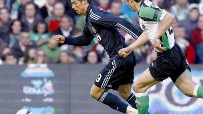 El delantero portugués del Real Madrid, Cristiano Ronaldo, conduce el balón, perseguido por el central del Racing de Santander José Moratón.