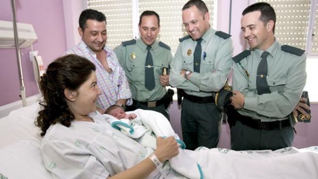 Eduvigis posa con su hijo recién nacido junto a su marido Francisco y los agentes de la Guardia Civil de Tráfico de Sevilla que le ayudaron.