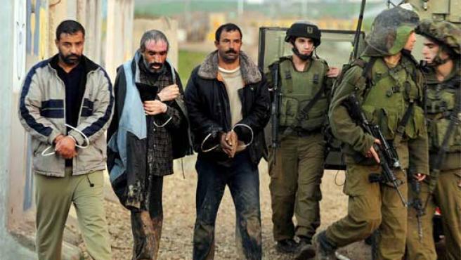 Soldados israelíes escoltan a tres de los palestinos arrestados en Cisjordania.