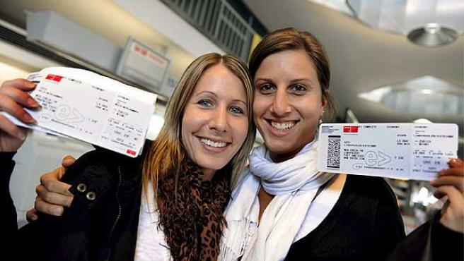 Dos jóvenes afortunadas muestran sus tarjetas de embarque antes de volar a Miami desde el aeropuerto de Zúrich, Suiza.