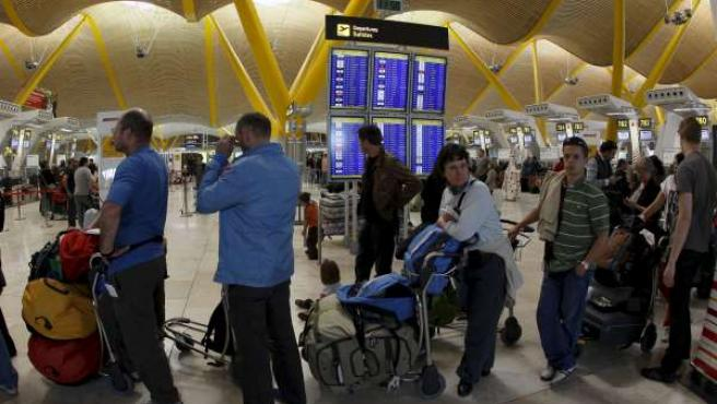 Varios pasajeros hacen cola ante un mostrador de la T4 del aeropuerto de Madrid-Barajas, donde la situación ha mejorado gracias a la apertura de los espacios aéreos de varios países europeos.