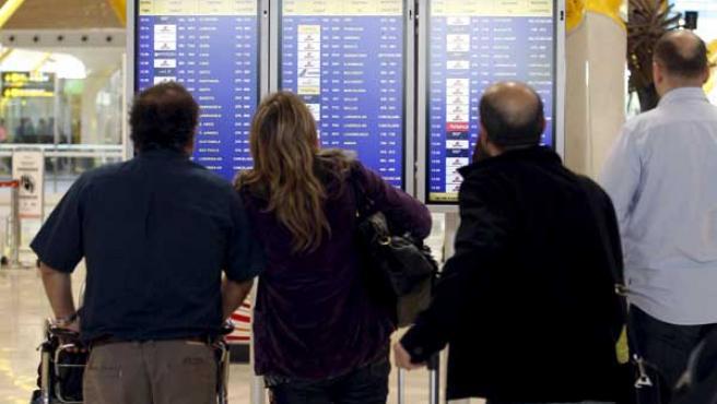 Pasajeros consultando la información de salida de vuelos en Barajas.