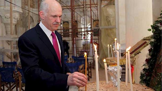El primer ministro griego, Yorgos Papandreu, encendiendo una vela en una iglesia de la isla de Kasterolizo.