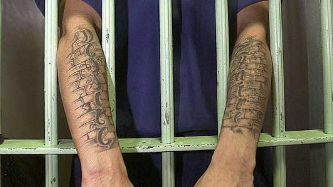 Un preso muestra sus brazos a través de los barrotes de su celda.