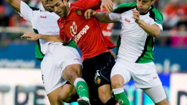 El delantero del Mallorca, Casadesus, defiende el balón ante los jugadores del Racing, Colsa (i) y Henrique.