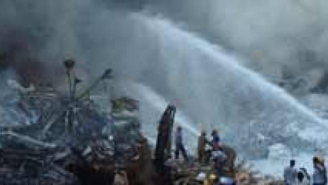 Equipos de emergencias ayudan a apagar el avión siniestrado en la India