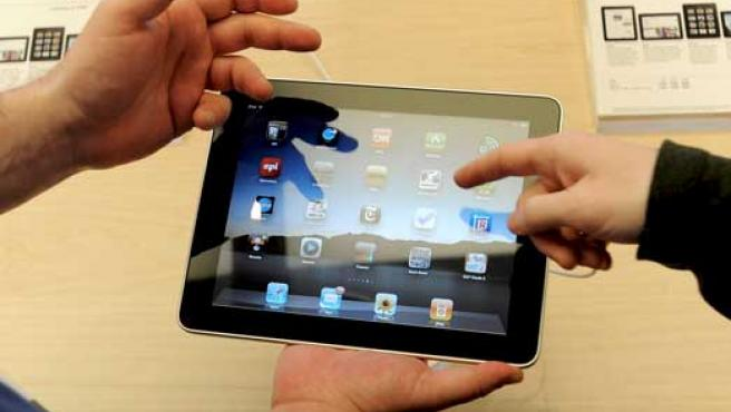 Dos personas prueban el iPad.