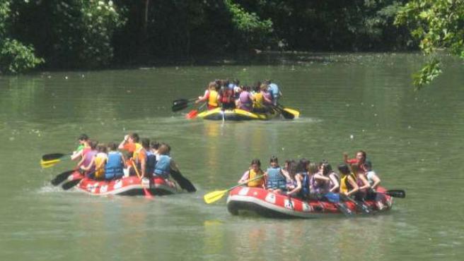 Alumnos navarros bajan en balsas por el río Arga.