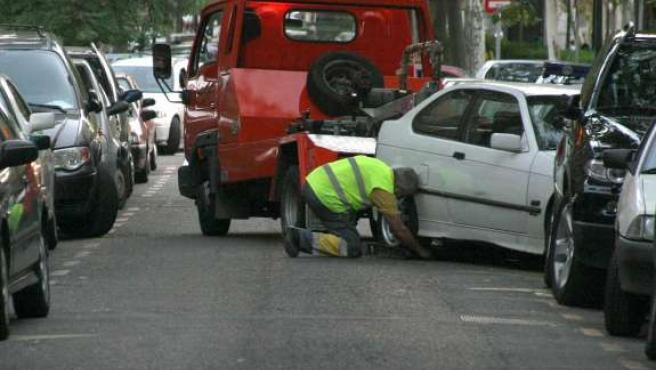 Una grúa retira un vehículo mal aparcado.