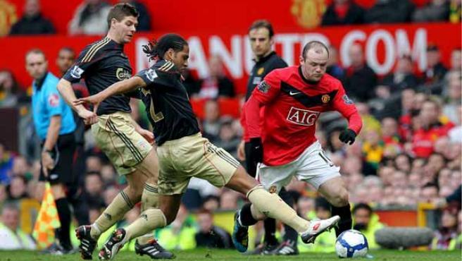 El delantero del Manchester United, Wayne Rooney, defiende el balón ante los jugadores del Liverpool, Steven Gerrard y Glen Johnson.