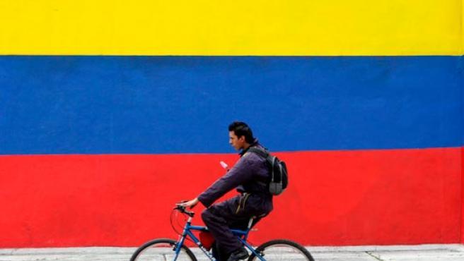 Un ciclista pasea por una calle de Bogotá adornada con una enorme bandera colombiana.