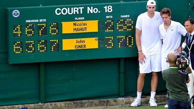 El estadounidense John Isner (d) y el francés Nicolás Mahut posan junto al tablero que señala el marcador.