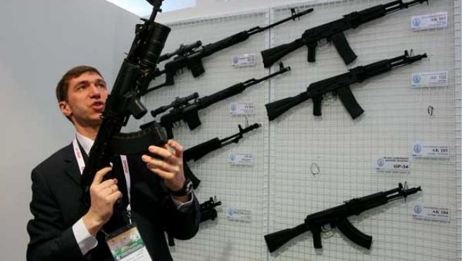 Un hombre muestra unos rifles en una feria de armamento.