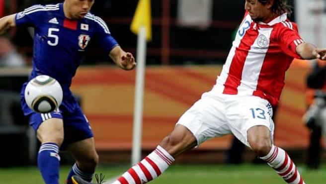 El paraguayo Enrique Vera (d) y el japonés Yuto Nagatomo disputan el balón durante el partido que las selecciones de Paraguay y Japón en octavos de final.
