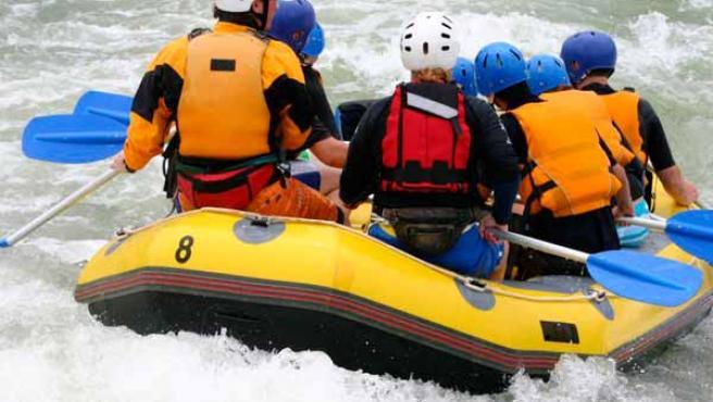 Un grupo de personas practica rafting.