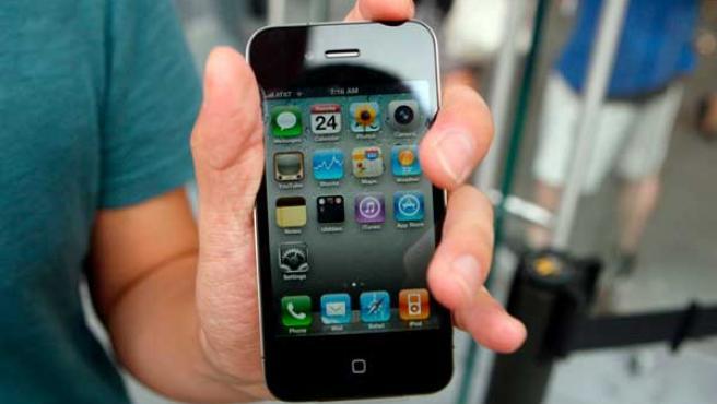 Un cliente muestra su iPhone 4 recién comprado.