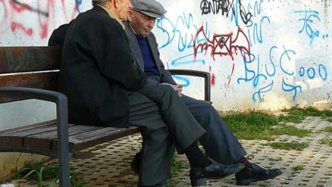 Dos ancianos conversan en un banco.