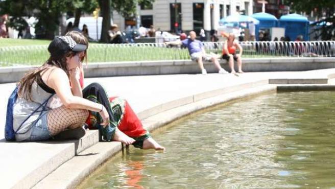 Dos jóvenes alivian el calor en una fuente