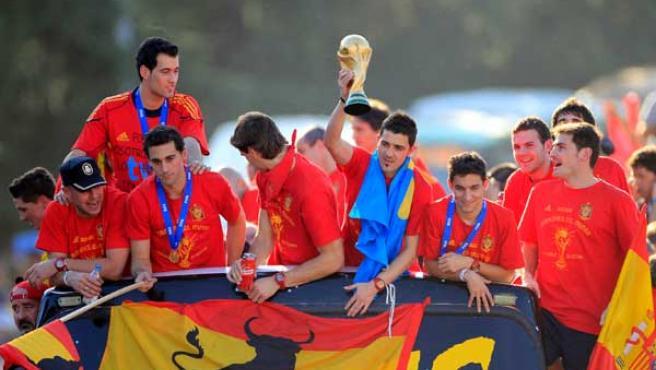 El delantero David Villa levanta la Copa junto a sus compañeros en el autobús que recorre las calles de Madrid.