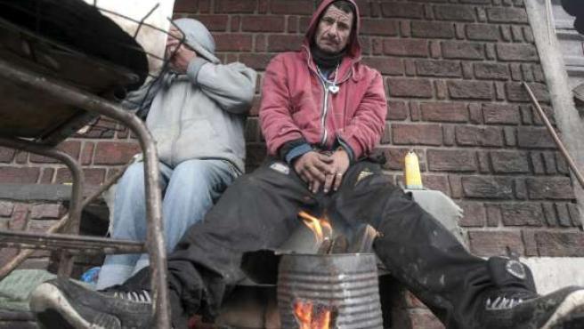 Un hombre se calienta las manos con fuego en una acera de la entrada de la Villa 31 en Buenos Aires (Argentina).