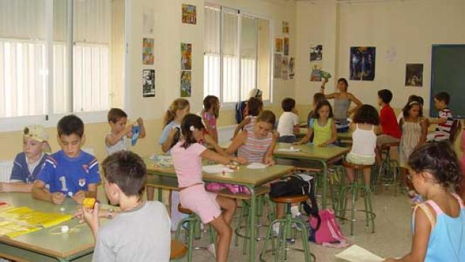 Varios niños asisten a una clase en un colegio.