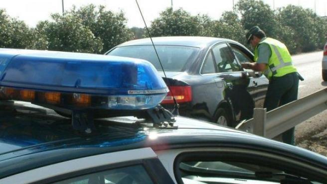 Un guardia civil realiza unas preguntas al conductor de un vehículo.