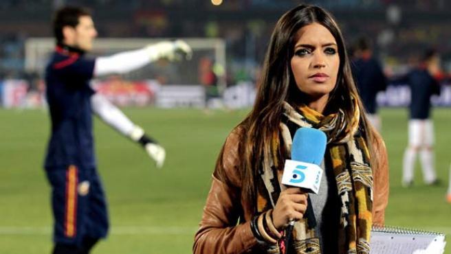 Sara Carbonero en el campo de juego; detrás, Iker Casillas.