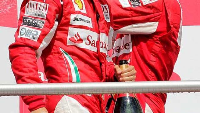 El piloto español Fernando Alonso (d), de Ferrari, y su compañero de equipo, Felipe Massa (i) celebran en el podio tras la carrera del Gran Premio de Alemania de Fórmula Uno.