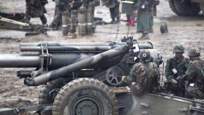 Un grupo de soldados norcoreanos descansan junto a una pieza de artillería.