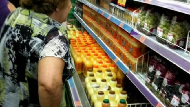 Una mujer realizando la compra en un supermercado.
