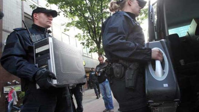 Dos policías salen con ordenadores confiscados de la mezquita de Taiba en Hamburgo.