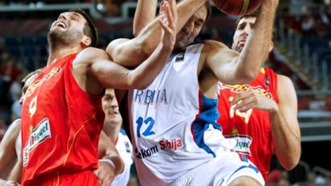 Los españoles Felipe Reyes (izda) y Álex Mumbrú pelean por el control del balón con el serbio Nanad Krstic.