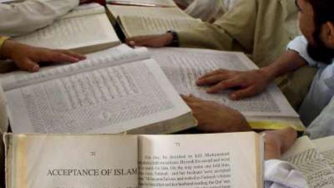 Varios fieles musulmanes leyendo el Corán.